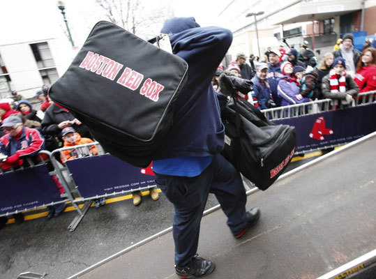 Fans watch as equipment is loaded onto the Red Sox moving truck outside Fenway Park in Boston.