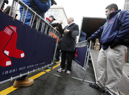Red Sox president and CEO Larry Lucchino (center) greets fans outside Fenway Park on Truck Day.