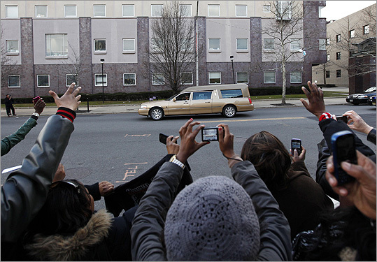 Fans waved as a hearse bearing the remains of Whitney Houston left the funeral.