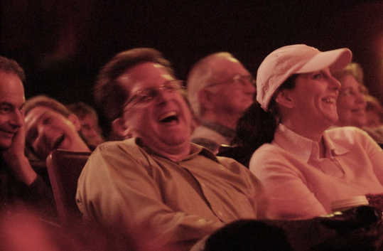 Drawing theater-goers into the suburbs is problematic, even in Arlington, located close to Boston, Cambridge and Somerville. Though many theater companies win awards and critical acclaim, such as the Fiddlehead Theatre in Norwood, they can't attract large enough audiences due to their location. The audience reacts as comedian Jimmy Tingle performs at the Regent Theatre in 2009.