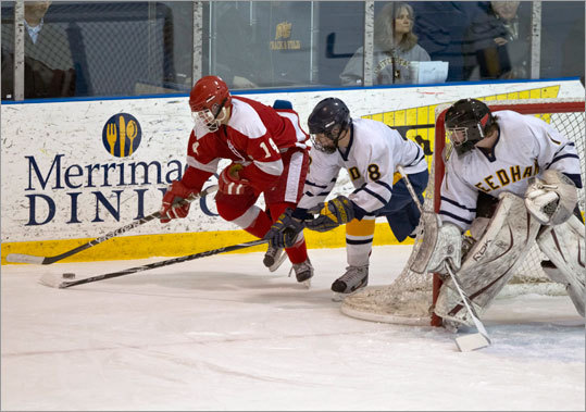 St. John's of Shrewsbury's Chris Coveney controlled the puck with pressure from Needham's Will Peterson and goalie Connor Murray.