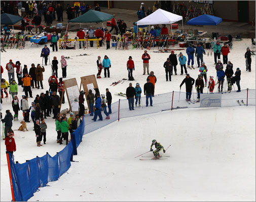 Despite the lack of snowfall, Wachusett Ski Area featured enough powder to for the state alpine ski championship to take place. A decent crowd looks on as one skier made his way to the finish line.