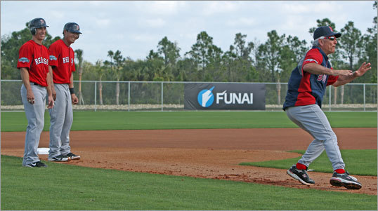 Red Sox manager Bobby Valentine did some hands on training as he showed players Nate Spears and Che-Hsuan Lin what he wanted them to do as they do a base running drill.