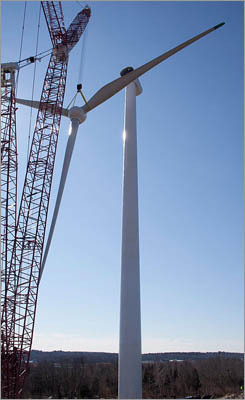 Shah expects the turbine to be operational by mid-March. Eventually, people may be able to monitor the electricity production through a website, and perhaps even view the turbine stats from their cell phones. The crane, just carrying the hub by two of the turbine blades, turned and swiveled on the crane to put the piece into position.