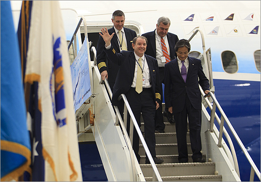Capt. Randy Neville, the chief pilot for the 787 Program for Boeing, waved to waiting journalists as he walked down the stairs with Hiroyuki Hioka, senior vice president for Japan Airlines in the Americas. Behind them were Boeing pilot Thomas Griffin, left; and Ed Freni, the director of aviation for MassPort.