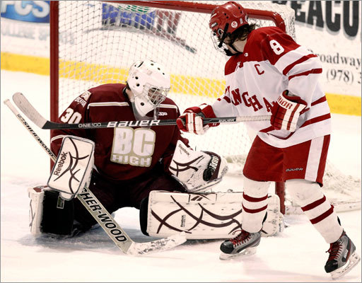 Hingham's Ryan Linehan goes toe to toe with BC High goalie Peter Cronin in the first round of the Super 8 ice hockey tournament at Merrimack College in North Andover. BC High went on to win the game 4-2.