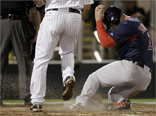 Boston's Kelly Shoppach covered his head as he scored on a wild pitch from Twins pitcher Jason Marquis in the second inning.