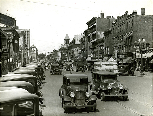 Working-class folks and families established roots near Central Square thanks to its quick access to the city. Immigrants also flocked to the area. The Central Square district is pictured in 1934. The busy traffic was typical of the brisk retail business center.