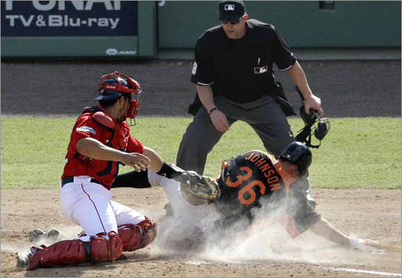 Baltimore's Nick Johnson beat the tag by Red Sox catcher Luis Exposito to scores off a double by Wilson Betemit in sixth inning of their Grapefruit League game Tuesday. The Red Sox beat the Orioles, 5-4.