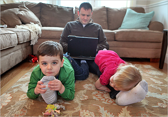 "David Mangan works on his laptop while hanging out with his children, Aidan and Keira. Sometimes he asks them to ""give me 10 more minutes,'' he says."
