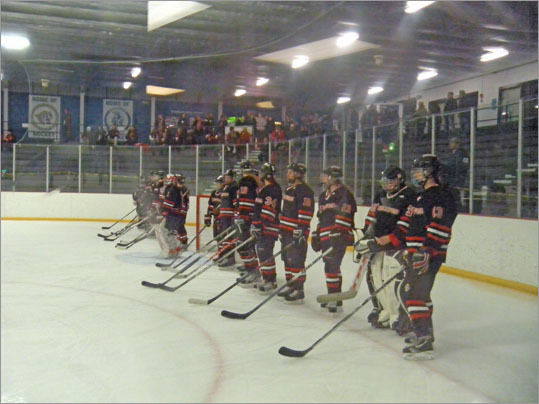 The Harborwomen line up before the puck drops to acknowledge their teammates and opponents and listen to the National Anthem performed by Westford's pep band.