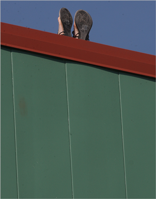 A fan seated atop the Green Monster relaxed with feet up.
