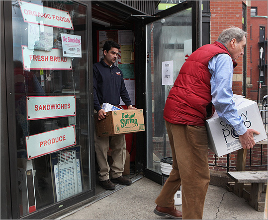 Owner Virgil Aiello (right) carried perishable foods from DeLuca's Market on Newbury Street and transferred them into a refrigerated truck parked nearby.