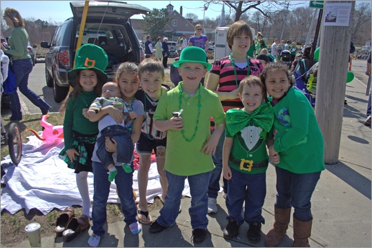 The Sullivan and Chiano families, from Marshfield, and the Coakley family, from Weymouth, enjoy the parade from the sidelines.