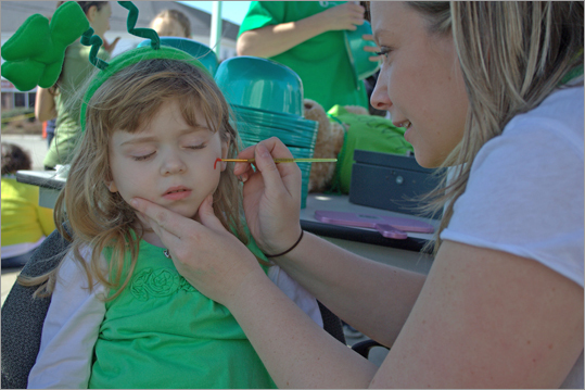 Molly Carey, 3, from Scituate, gets her face painted to help celebrate St. Patty's Day.