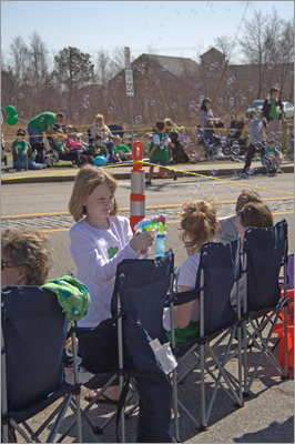 Samantha McDonough, 10, from Plymouth, plays with bubbles as she waits for the parade.
