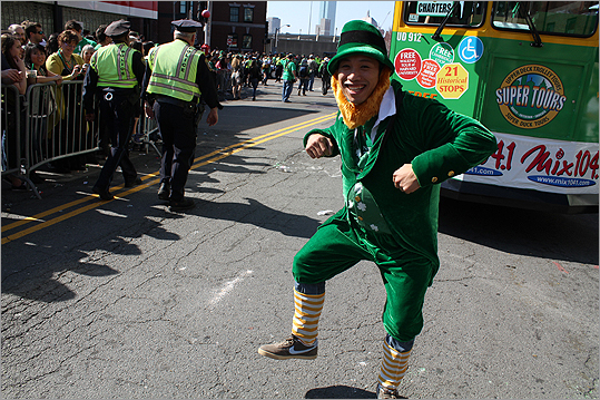 With good weather, hundreds of thousands of revelers stood along the streets of South Boston today for one of the country's signature St. Patrick's Day parades. Take a look at scenes from the festivities. A leprechaun is pictured dancing a jig.
