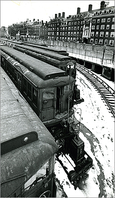 Constructing the Cambridge subway was difficult, with workers injured and killed. Business and residential life was disrupted as surface streetcars had to be rerouted from Main Street and Massachusetts Avenue onto temporary tracks nearby during excavation. This undated photo shows old MBTA trains waiting in Harvard Square yard to be moved to make room for the JFK library.