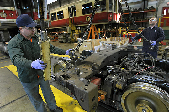 Repairmen Michael Romani, left, and Brendan Keeffe are pictured working on a Red Line train's wheels at the MBTA's Cabot yards in Boston.