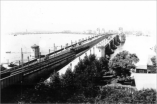 The laws that led to the creation of the first Boston subway lines in 1897 stipulated that the Boston Transit Commission construct a bridge over the Charles River that could be used by both street traffic and future public train lines. The Cambridge tunnel on the Longfellow Bridge was constructed in 1906-- six years before the subway was built. The bridge is pictured in 1912 as a train crosses.