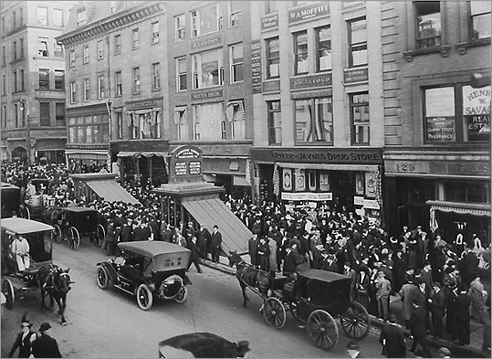 This 1913 picture shows lines of people waiting to get into the Park Street Under station on Tremont Street.