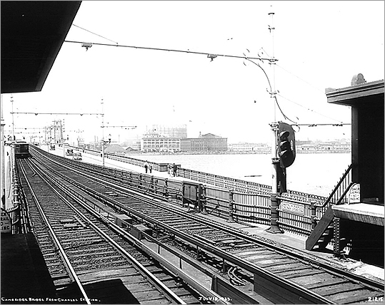Construction did not begin on the subway line until 1909, three years after the Longfellow Bridge was built, due to local conflicts. Cantabrigians wanted five stops between Harvard and the Charles River, while suburbanites farther north wanted only one stop between them and Boston. At hearings, Cambridge brought in experts who stated that long, station-free rides would be hazardous to one's health due to 'mephitic exhalations.' Officials compromised and allowed two stations other than Harvard's. A train is pictured pulling into Charles St. Station in 1933.
