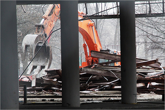 A hydraulic shovel is pictured at the beginning of demolition at Macy's in Chestnut Hill.