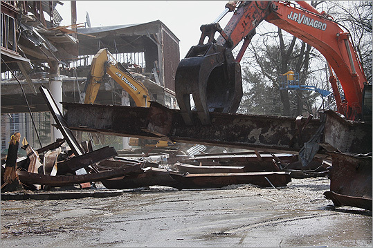 Crews started bringing down the former Macy's building in the Chestnut Hill Shopping Center on Wednesday. Over the next three weeks, all signs of the 120,000-square-foot building will be removed, said Dick Marks, a partner in WS Development, which owns the property.