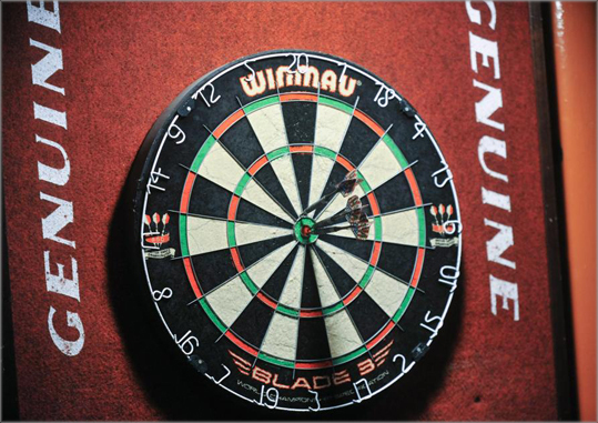 Tuesday night is darts night at the Tavern, a downtown Framingham watering hole. Patrons of all ages and skill levels can join one of a number of colorfully named teams that make up the Minute Man Dart League. The dart board at the center of the action at The Tavern.