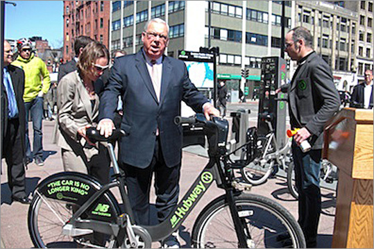"""Freedman presents Boston Mayor Thomas M. Menino, an avid bicycle rider, with his own Hubway bicycle with the phrase """"The car is no long king,"""" a favorite phrase of Menino's, written on the back wheel. """"We are going to keep up the good work and keep making improvements in our program,"""" Menino said, before encouraging cyclists to wear helmets and use lights at night. The city has also been working to educate drivers and bicyclists on how to share the road. """"The bottom line, folks, is this: we all share the road, so we all have to share the rules,"""" Menino said."""