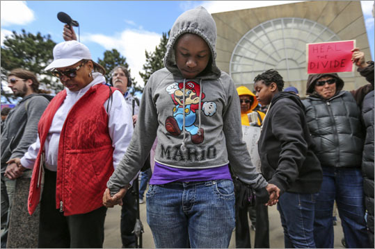 Kailah Hicks, 11 (center), joined hands with fellow protesters during a prayer before a march from Ruggles Station to Dudley Square on April 7.