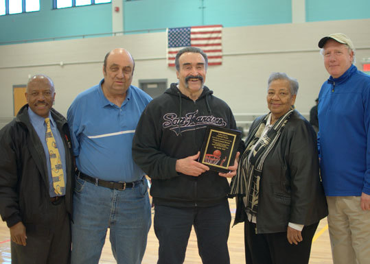 After 28 years as the Washington Irving Middle School boys' basketball coach, Leonard Brown (center) was honored during the Middle School Basketball Championships at the Shelburne Community Recreation Center. Also photographed from left to right is Boston Public Schools athletic director Ken Still, official scorer Al Brodsky, school committee member Alfreda Harris and Brown's friend and former colleague Stan Litchman.