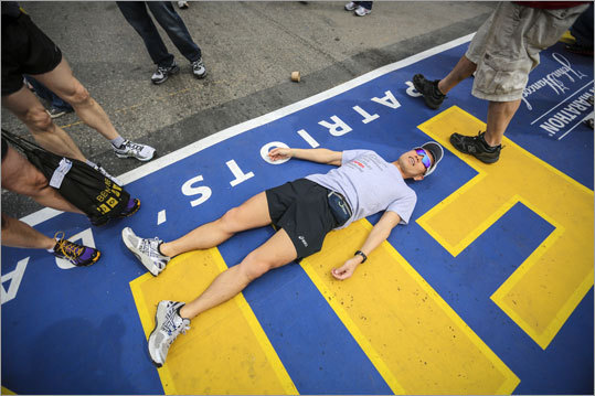 Chris Imai, 42, of Vancouver, posed for photos on the finish line of the Boston Marathon route on Boylston Street in Boston. He will be running the marathon Monday.