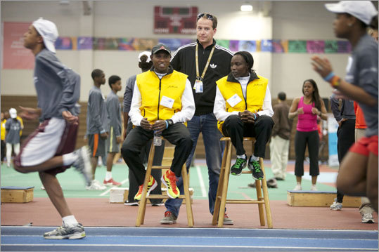 Geoffrey Mutai, the defending Boston marathon champion, and Caroline Kilel (right) trained with Boston Public High School track teams at the Reggie Lewis Track and Athletic Center in Roxbury on Wednesday. Also pictured is Mutai and Kilel's agent Arien Verkade (center).