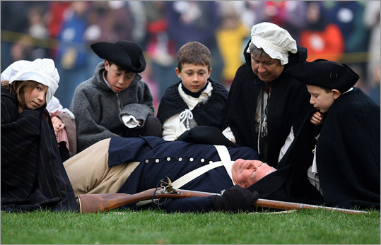 Jim Hart who plays Jonas Parker, the first to be killed , bayoneted by Redcoat, is surrounded by his wife Myra and grandchildren during the 38th Re-Enactment of the Battle of Lexington . He has been part of the re-enactment for 36 years.