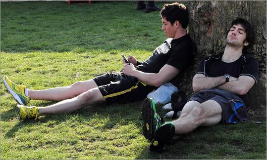 Two rest on Hopkinton Common before the start of the 2012 Boston Marathon.