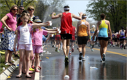 Jessica Coomber, 8, and her John Ward Schoolmates spend the start of their spring break handing out water to runners on Commonwealth Avenue.