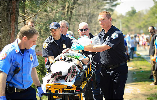 A female runner who collapsed near the half-way mark was taken away via stretcher by Wellesley fire department members during the Boston Marathon on April 16, 2012.