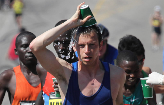 Elite runner Nicholas Arciniaga cooled off on the course during the Boston Marathon.