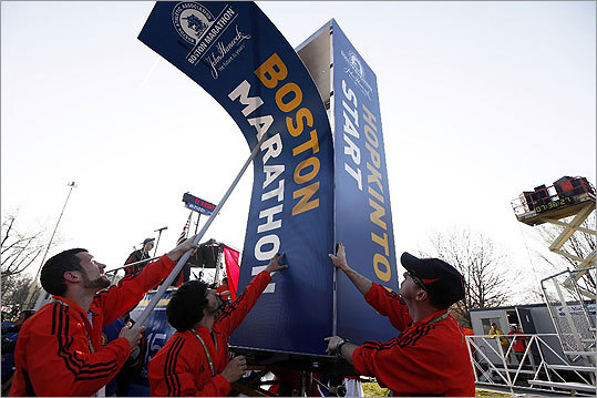 Boston Marathon workers fixed signs at the start line in Hopkinton.