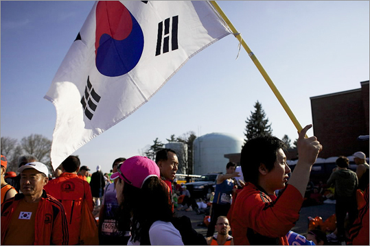 Sunghoon Cho waved the South Korean flag before the start of the 2012 Boston Marathon.