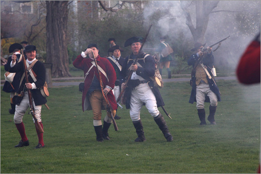 Minutemen re-load and try to fight back against the British among the chaos on the Green and spectators surrounding the action.