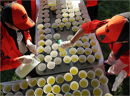 Volunteers filled cups at the Athlete's Village prior to the start of the race.