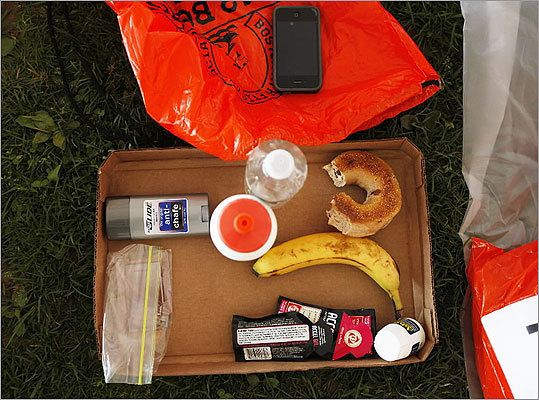 A box of essentials - body glide, water, bagel, banana, advil, and Accel Gel - sat near a runner before the race