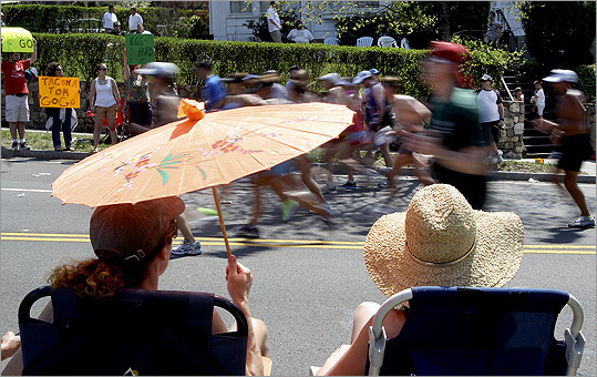 Jen Schoenberg (left) and Mary Hawes were appropriately accessorized for the heat as they watched runners on Heartbreak Hill.