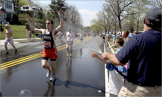 Joe Verdone (right) offered cooling relief with his garden hose for runners climbing Heartbreak Hill, which Thomas Schnitzer of Cambridge, Mass., enjoyed.