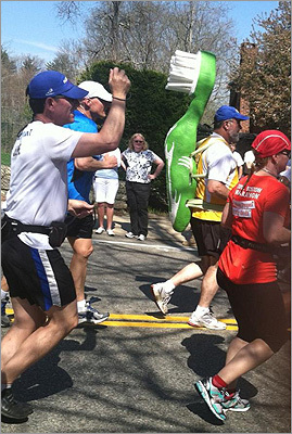 A man in the pack ran with a giant toothbrush strapped to his back.