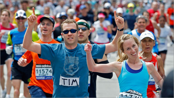 A couple of happy runners cross the finish line at the 114th Boston Marathon.