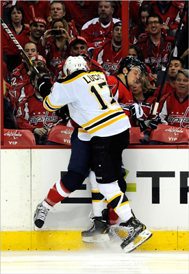 John Carlson of the Capitals and Milan Lucic of the Bruins battle against the glass.