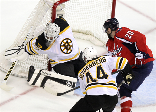 Bruins goalie Tim Thomas pinned the puck against the net as onrushing Capitals left wing Troy Brouwer looked for the rebound.